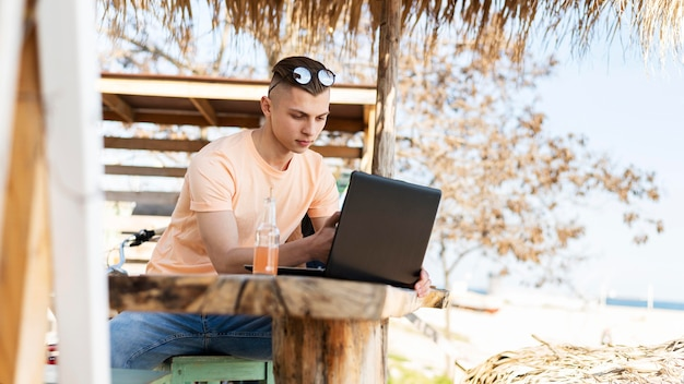Mężczyzna pracujący na laptopie na zewnątrz