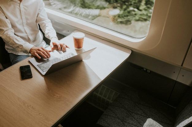 Mężczyzna pracujący na laptopie podczas podróży służbowej pociągiem