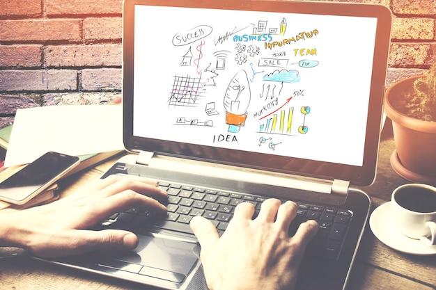 Mężczyzna pracujący na laptopie siedząc przy drewnianym biurku