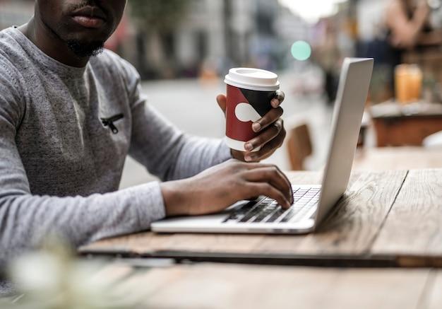 Mężczyzna pracujący na laptopie w kawiarni