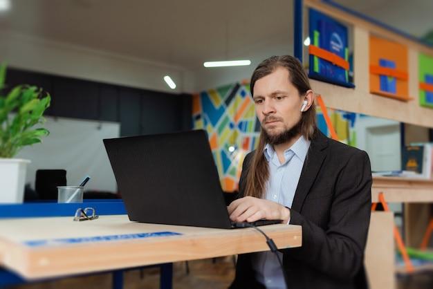 Mężczyzna pracujący na laptopie w kolorowym coworkingu