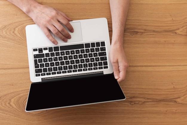 Mężczyzna pracujący na laptopie, widok z góry na męskich rękach za pomocą laptopa