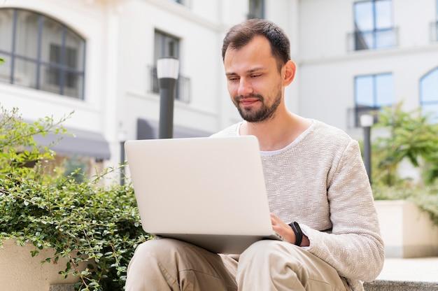 Mężczyzna pracujący na zewnątrz na laptopie