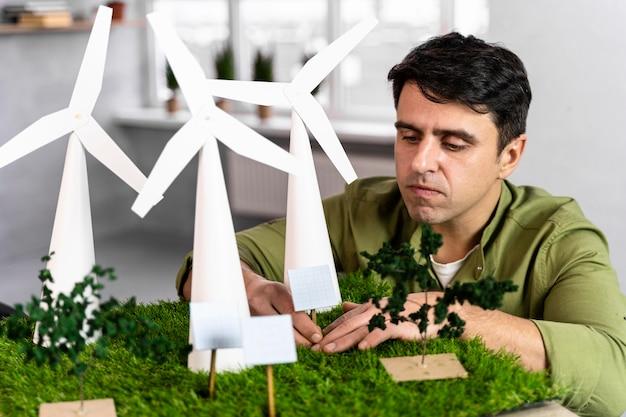 Mężczyzna pracujący nad projektem ekologicznej energii wiatrowej z turbinami wiatrowymi