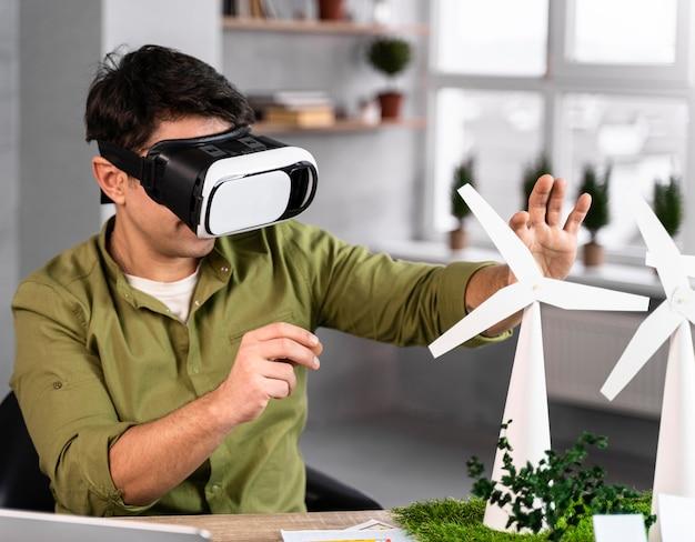 Mężczyzna pracujący nad projektem ekologicznej energii wiatrowej z zestawem słuchawkowym do wirtualnej rzeczywistości