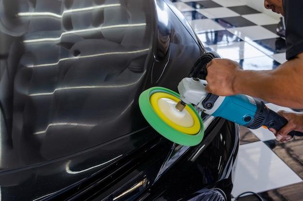 Mężczyzna pracujący przy polerowaniu, malowaniu samochodów. polerowanie auta pomoże wyeliminować zabrudzenia z powierzchni auta.