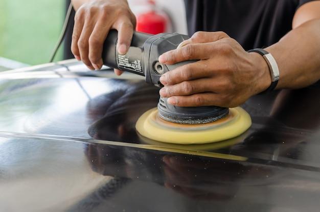 Mężczyzna pracujący przy polerowaniu, malowaniu samochodów. polerowanie auta pomoże wyeliminować zanieczyszczenia z powierzchni auta