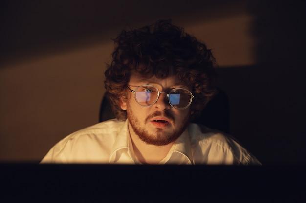 Mężczyzna pracujący sam w biurze podczas koronawirusa lub kwarantanny covid-19, pozostający do późnej nocy