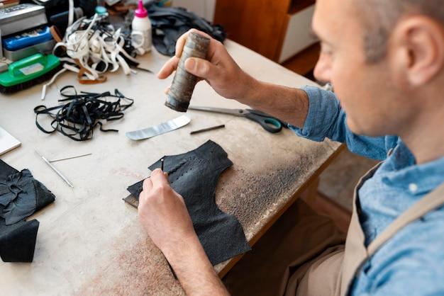 Mężczyzna pracujący samotnie w warsztacie skórzanym