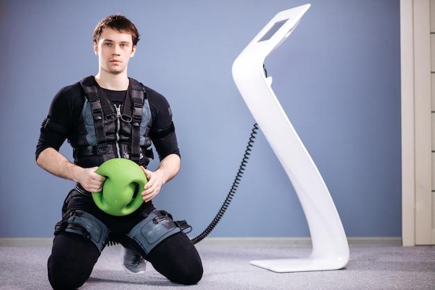 Mężczyzna pracujący trening ems z piłką medyczną