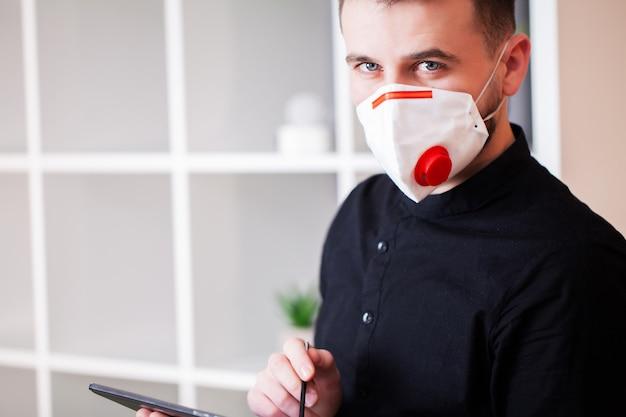 Mężczyzna pracujący w biurze na sobie maskę do ochrony przed koronawirusem