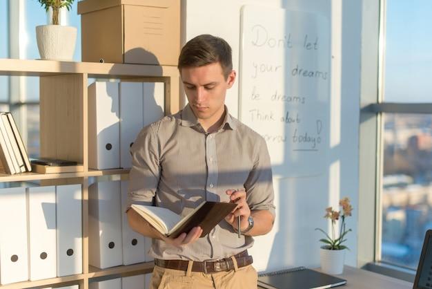 Mężczyzna pracujący w biurze, planujący zadania, zapisujący swój harmonogram do planisty w miejscu pracy.