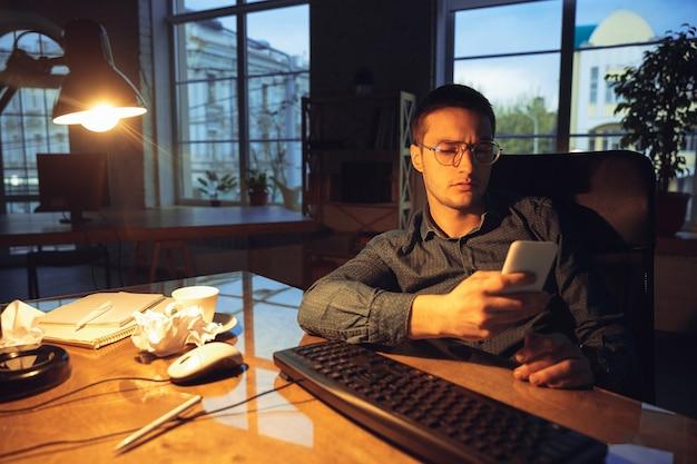 Mężczyzna pracujący w biurze sam, przebywający do późnej nocy.