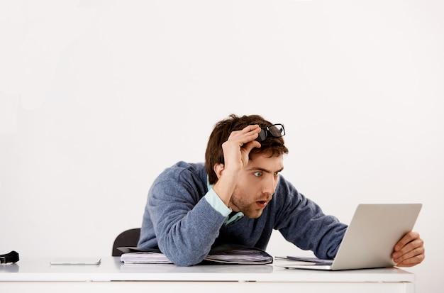 Mężczyzna pracujący w biurze, zdejmujący okulary i wpatrujący się w zmieszanie z niedowierzaniem ekran laptopa, czytający szokujące wiadomości, otrzymuje ciekawy raport