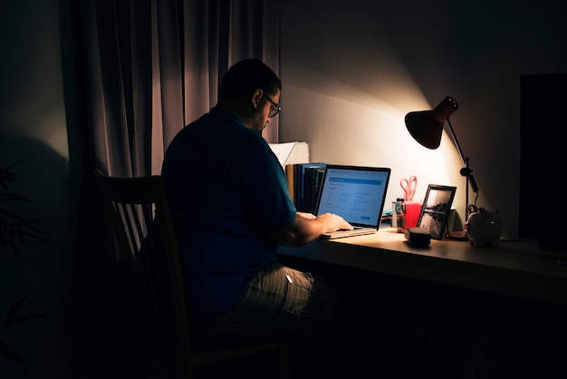 Mężczyzna pracujący w ciemnym biurze domowym z laptopem