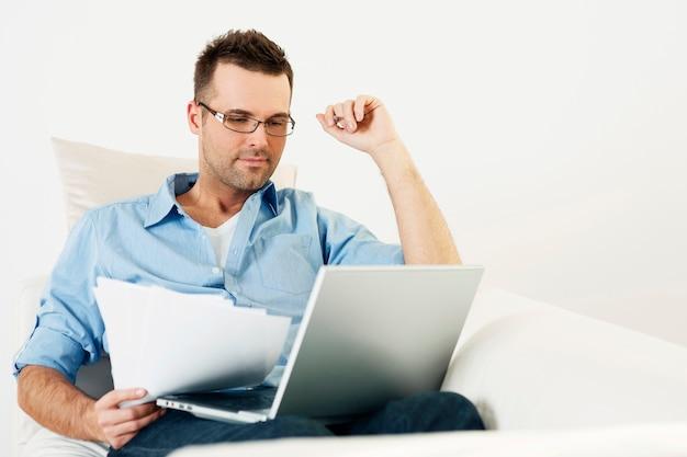 Mężczyzna pracujący w domu z laptopem