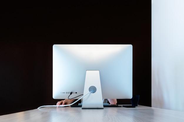 Mężczyzna pracujący w domu z nowoczesnym komputerem widziany od tyłu z brązowym tłem