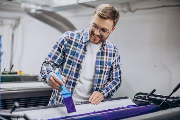 Mężczyzna pracujący w drukarni z papierem i farbami