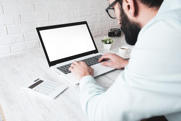 Mężczyzna pracujący w komputerze i kalkulatorze na biurku