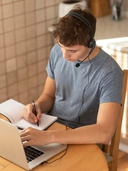 Mężczyzna pracujący w kuchni w domu podczas kwarantanny z laptopem
