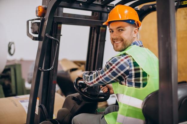 Mężczyzna Pracujący W Magazynie I Prowadzący Wózek Widłowy Premium Zdjęcia
