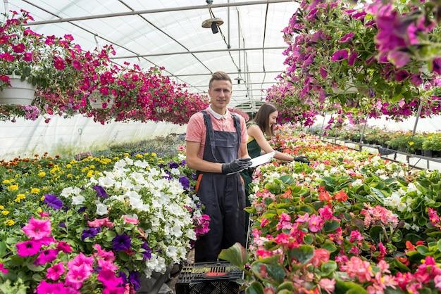 Mężczyzna pracujący w słonecznej oranżerii pełnej kwiatów sprawdza stan roślin w przemysłowej szklarni