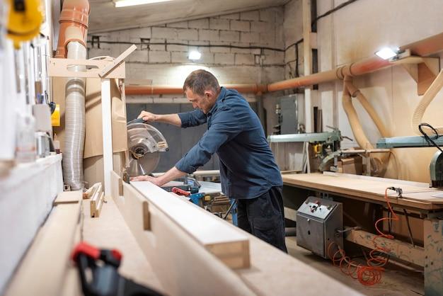 Mężczyzna pracujący w warsztacie drewna