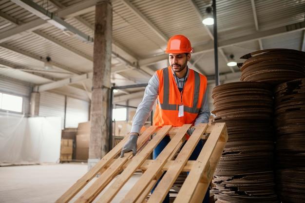 Mężczyzna pracujący z ciężkimi materiałami drewnianymi