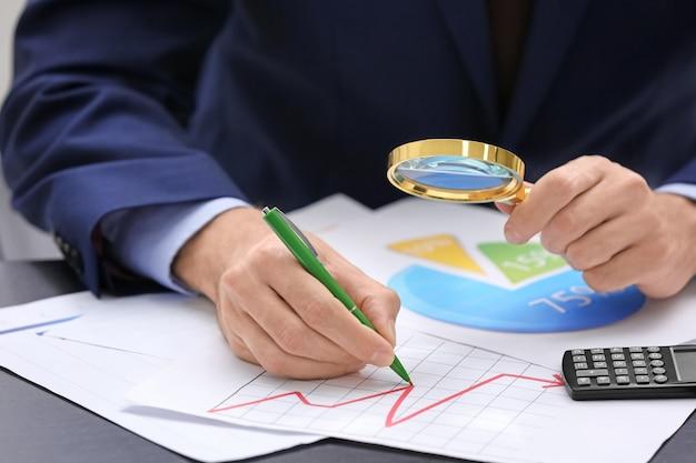 Mężczyzna pracujący z dokumentami przy stole. koncepcja forex