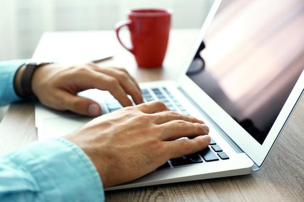Mężczyzna pracujący z laptopem w biurze