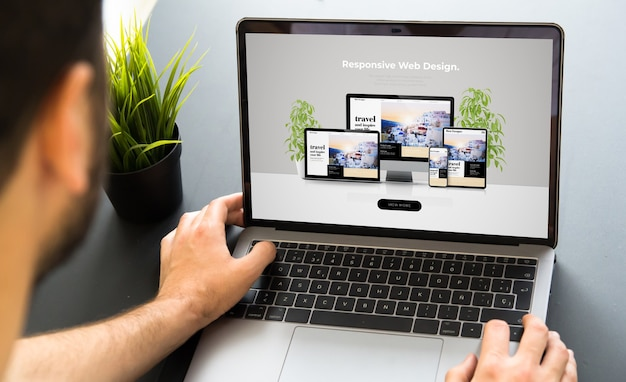 Mężczyzna pracujący z makietą laptopa na ekranie projektowania responsywnej strony internetowej