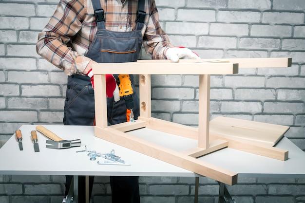 Mężczyzna pracujący z montażem mebli za pomocą elektrycznego śrubokręta na szarym tle cegieł