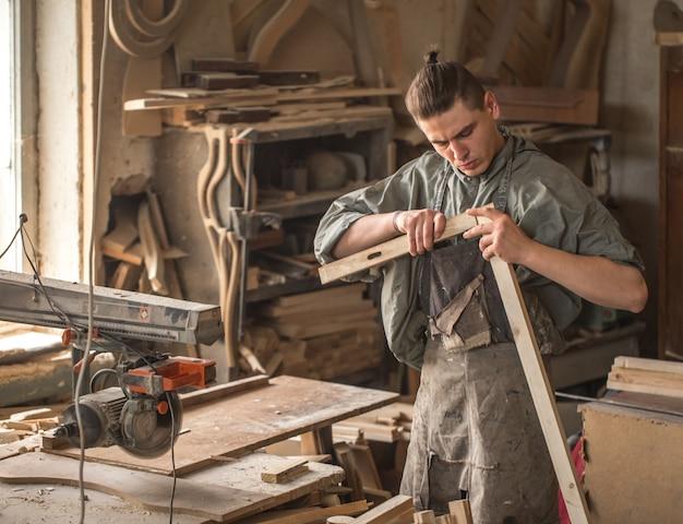 Mężczyzna pracujący z produktem drewnianym na maszynie