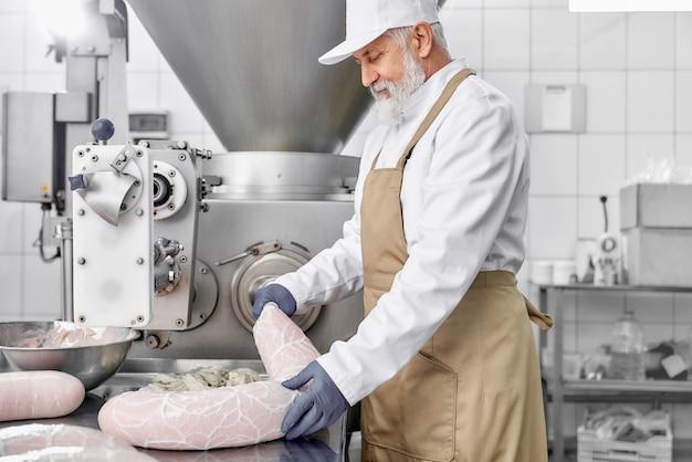 Mężczyzna pracujący z wyposażeniem do produkcji kiełbas.