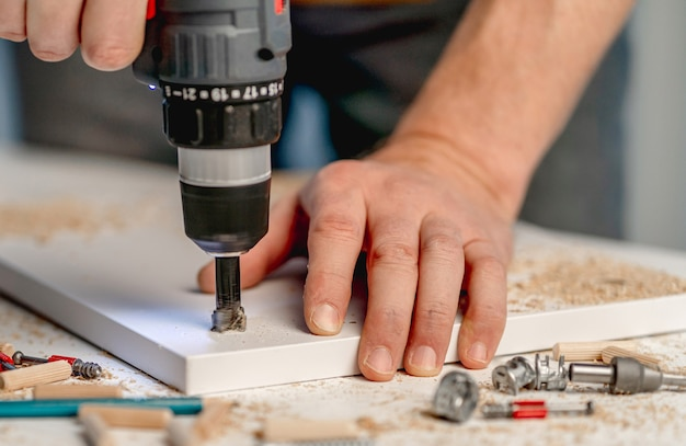 Mężczyzna pracujący za pomocą elektrycznego śrubokręta podczas procesu produkcji mebli drewnianych