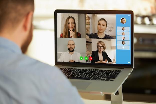Mężczyzna pracujący zdalnie podczas rozmowy wideo na komputerze w domu