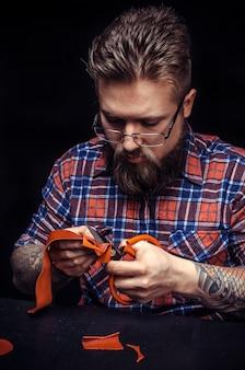 Mężczyzna pracujący ze skórą pracujący nad nowym produktem skórzanym w warsztacie.