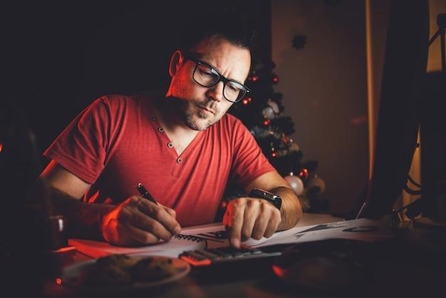Mężczyzna pracuje do późna i pisze w notatniku