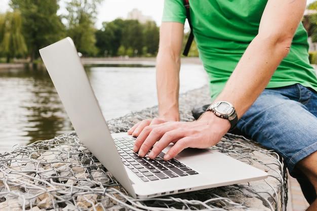 Mężczyzna pracuje na laptopie nad jeziorem