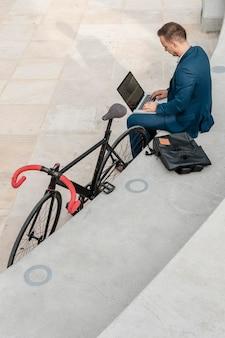 Mężczyzna pracuje na laptopie obok swojego roweru