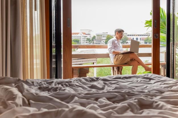 Mężczyzna pracuje na laptopie przy hotelowym balkonem