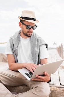 Mężczyzna pracuje na laptopie przy plażą