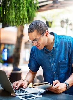 Mężczyzna pracuje na laptopie przy restauracją
