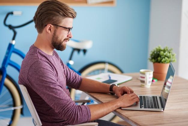 Mężczyzna pracuje na laptopie w domu