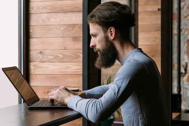 Mężczyzna pracuje na laptopie w kawiarni