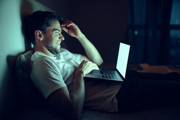 Mężczyzna pracuje na laptopie w łóżku, ukochana kobieta śpi, praca w nocy, zdrada
