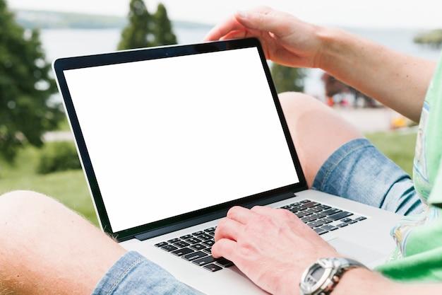 Mężczyzna pracuje na laptopie w parku