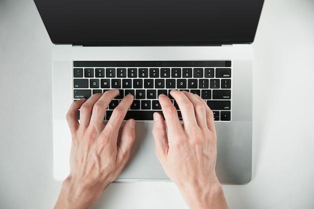 Mężczyzna pracuje na laptopie w widoku z góry