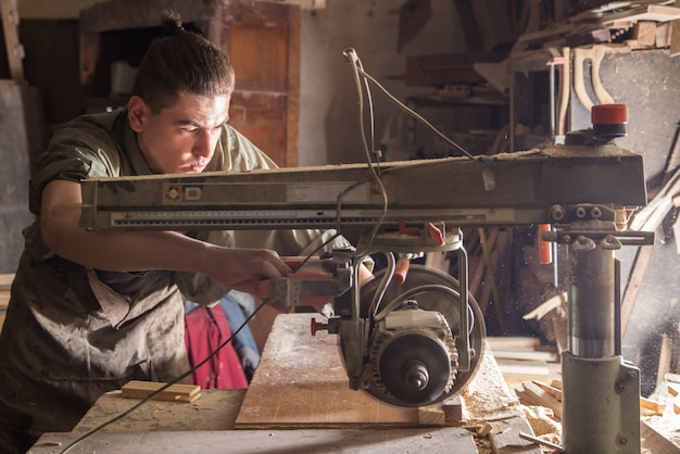 Mężczyzna pracuje na maszynie z drewnianym produktem
