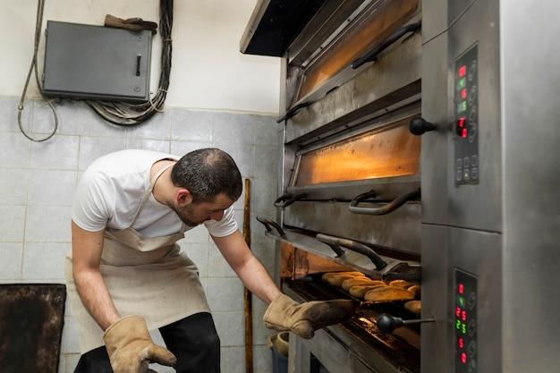 Mężczyzna pracuje na pyszne świeże pieczywo